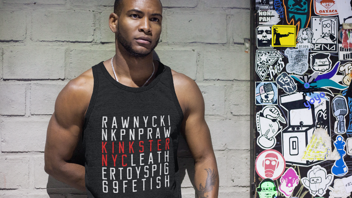 African-American man wearing a Kinkster NYC tri-blend tank top standing against a subway wall.