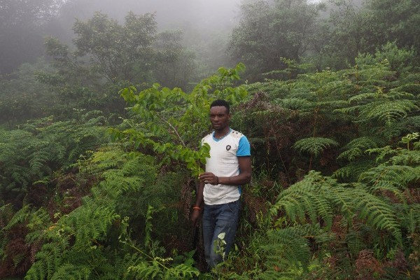 Local guide, James, with a tree he planted during the reforestation project. ©  Kevin Cox