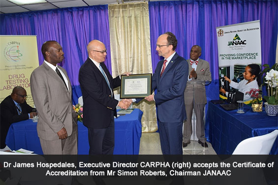 Dr James Hospedales, Executive Director CARPHA (r) accepts the Certificate of Accreditation from Mr Simon Roberts, Chairman JANAAC