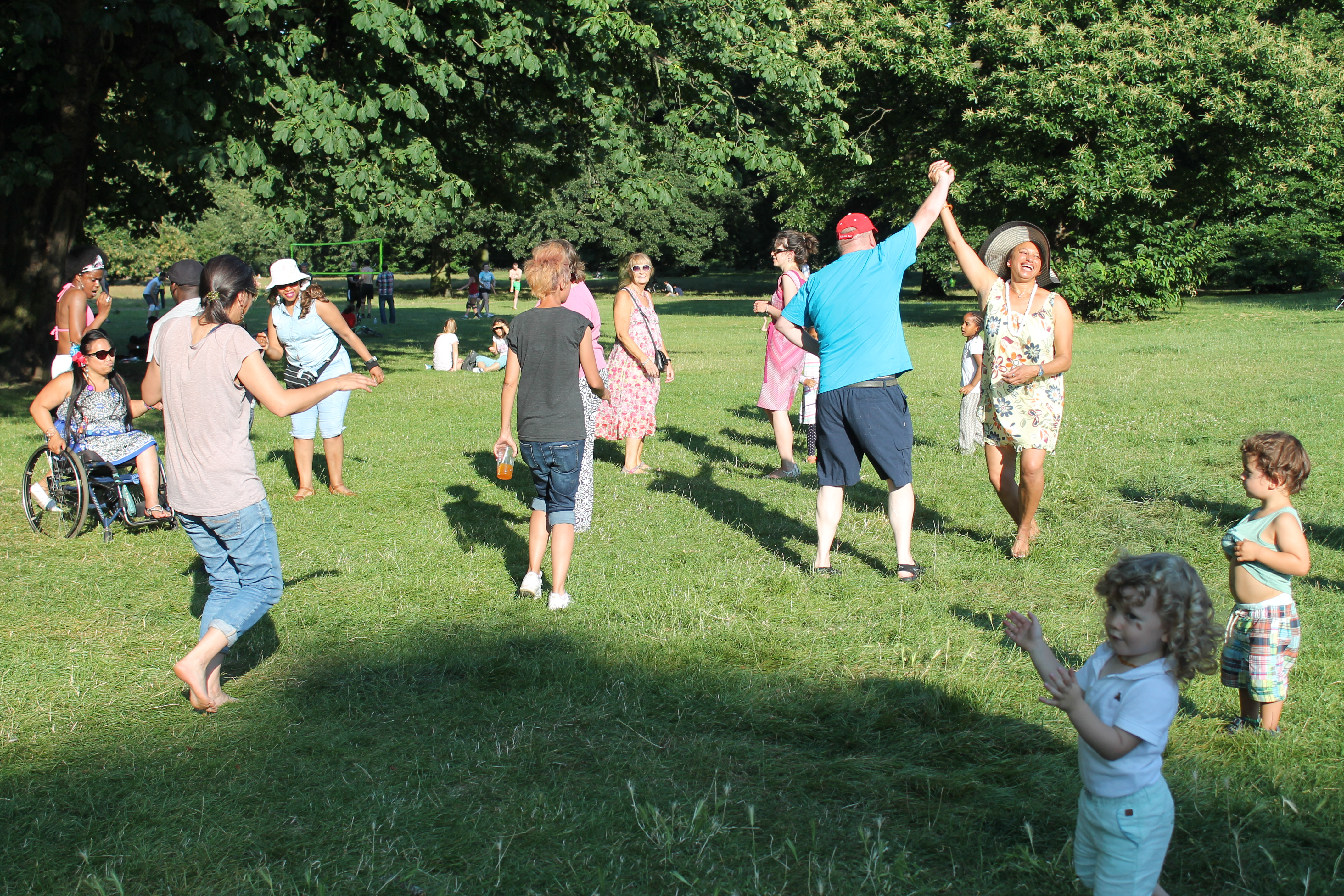 Photo 4: A Dance in the Park, everyone is dancing in the park, joined by some children and parents