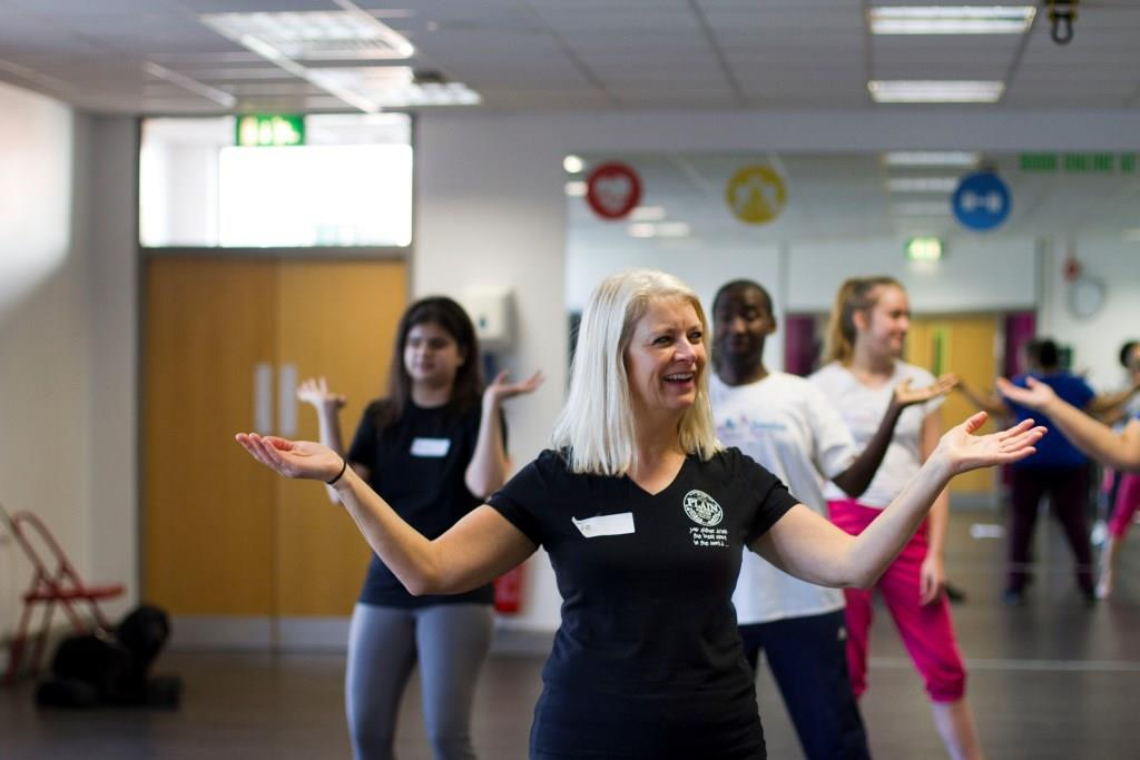 Jo R smiles as she learns a VI Zumba arm move; Uzma, Mickel and an ILF volunteer smile and learn the move in the background.