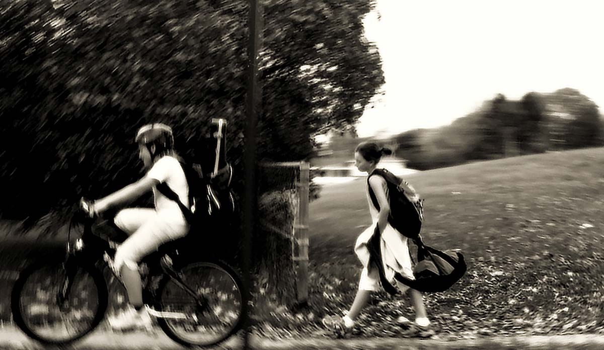 A boy riding a bike and a girl walking along a rural road