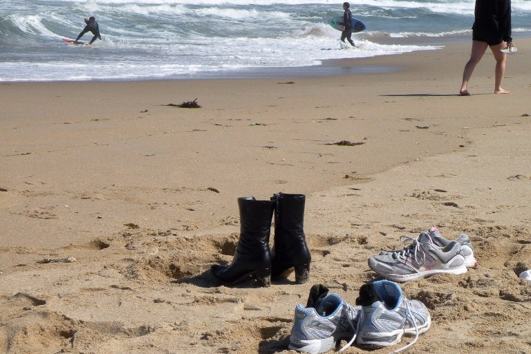 Image of beach with water in background and abandoned running shoes and socks in the foreground.