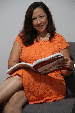 Marisol Barrios sitting down smiling while holding a public relations textbook