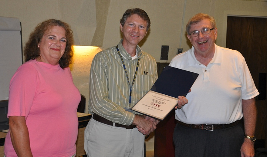 FLC Officials, Valerie Larkin and Gaetan Mangano, present Griffiss Institute Principal Engineer James Cusack with the FLC Industry / Non-Federal Government  / University Award for Griffiss Institute.