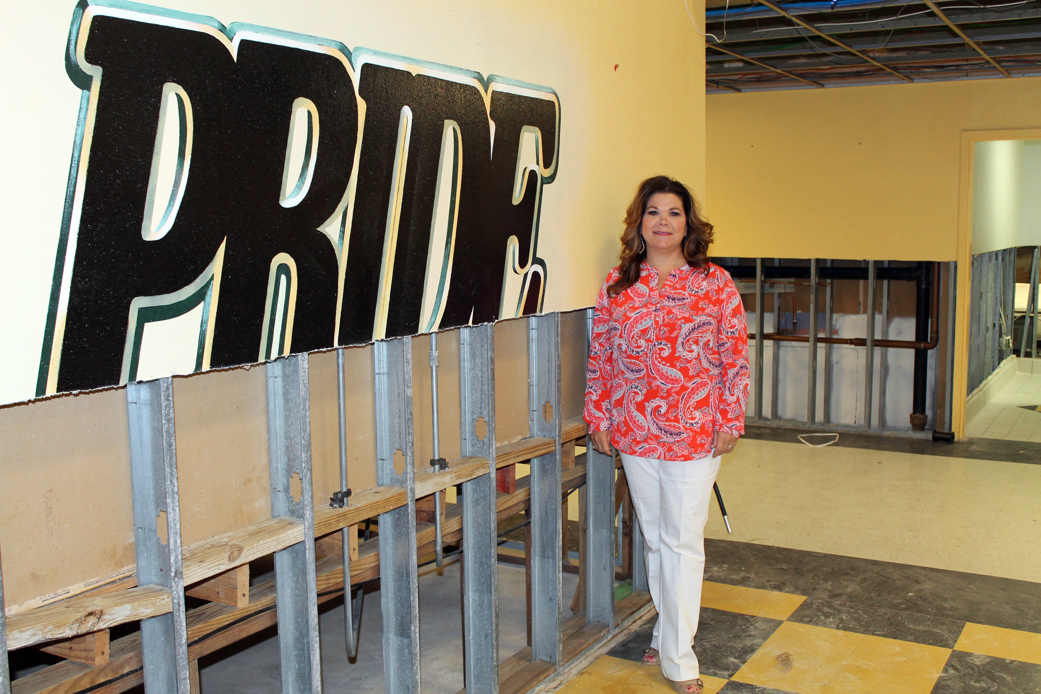 "Mia Edwards next to a gutted wall with the word ""Pride"""