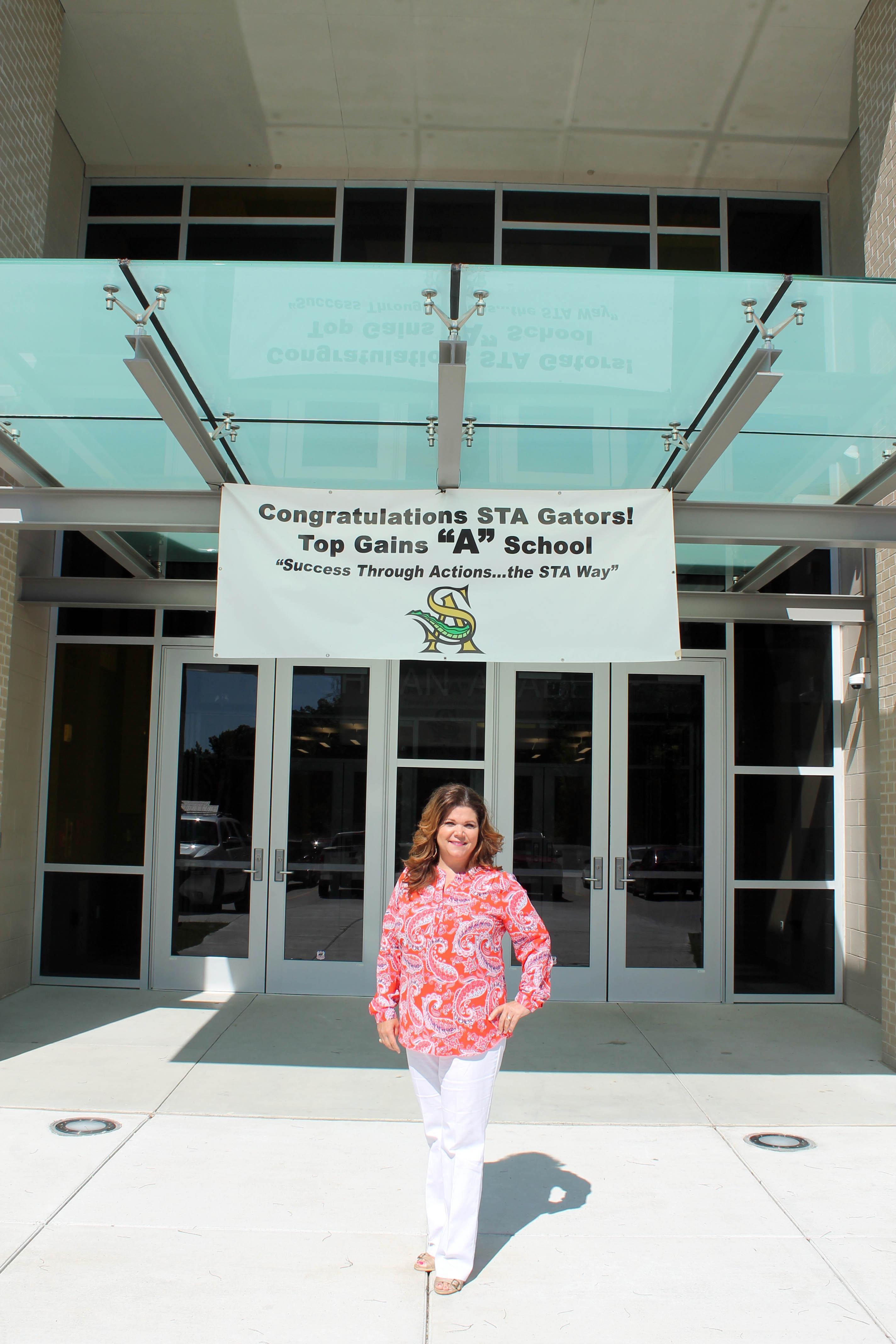 "Mia Edwards before a sign ""Congratulations Top Gains School"""
