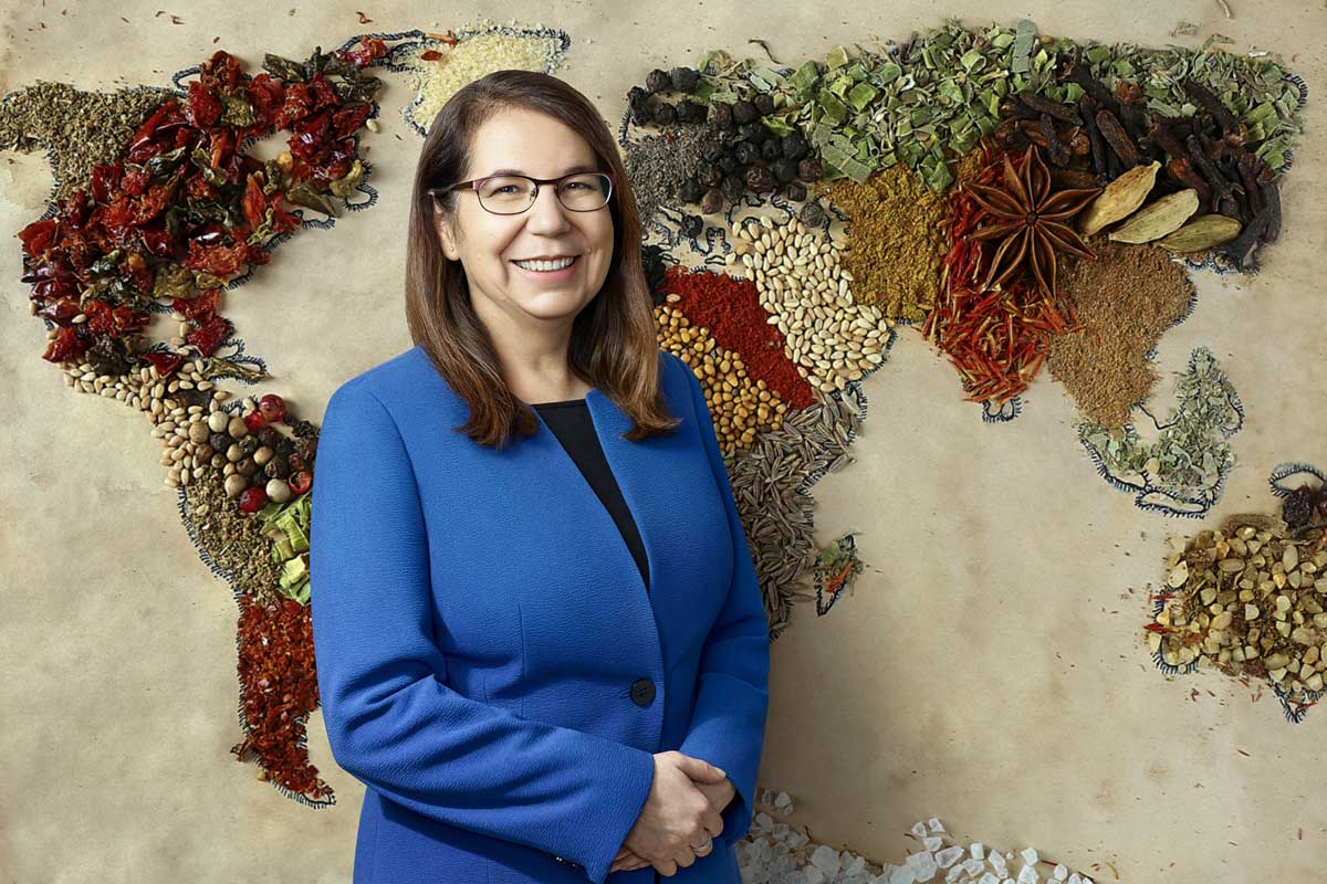 Smiling woman wearing blue blazer standing in front of world map made from different types of food