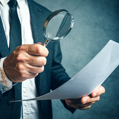 A hand holding a magnifying glass over a paper