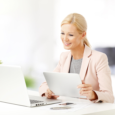 A businesswoman looking at a laptop and holding a tablet on hand