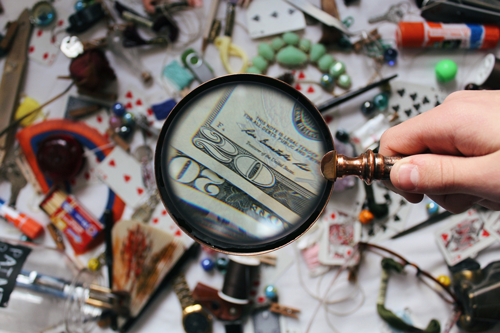 Photo of magnifying glass hovering over money.