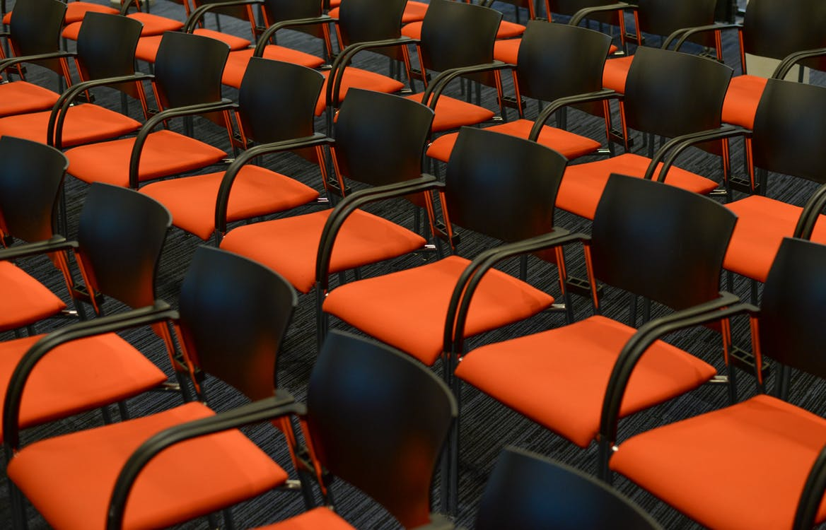 Photograph of empty seats in a conference room.
