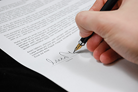 Photograph of an individual signing a document.