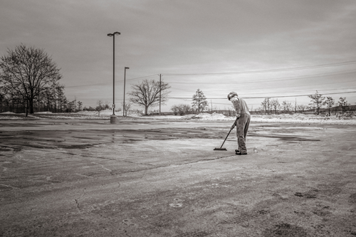 Photograph of man sweeping in parking lot.