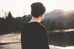 Photograph of young man looking at lake