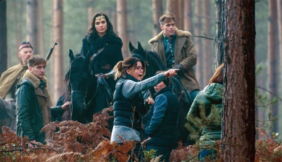 Patty Jenkins directs actors Gal Gadot and Chris Pine, on horseback in a wooded area, in the 2017 blockbuster Wonder Woman.