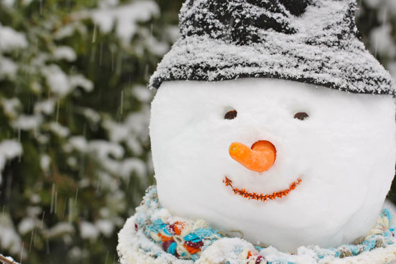 A snowman with a stocking cap and carrot nose.
