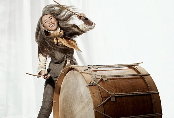 A woman is playing a very large drum.