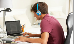 Young man sits at desk, typing on laptop and wearing headphones.