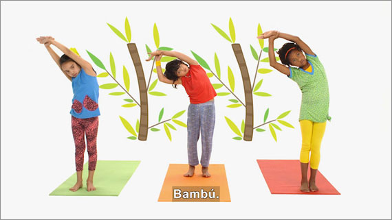 Three children stand on yoga mats and stretch to their right.