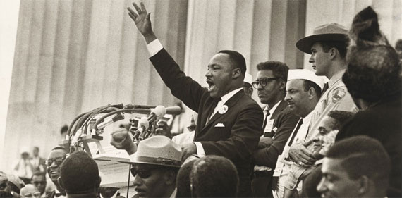 On the steps of the Lincoln Memorial, surrounded by several other men and park rangers, Martin Luther King, Jr. speaks at a podium covered with microphones, his right arm outstretched.