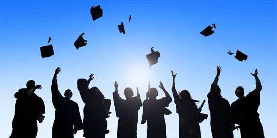 Silhouette of several students tossing graduation caps in the air.