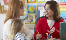A teacher, parent, and young girl have a conversation in the classroom.