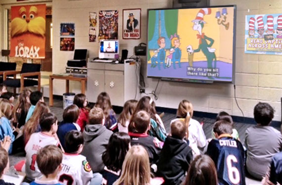 Children in a classroom watch a Cat in the Hat video on a large screen.