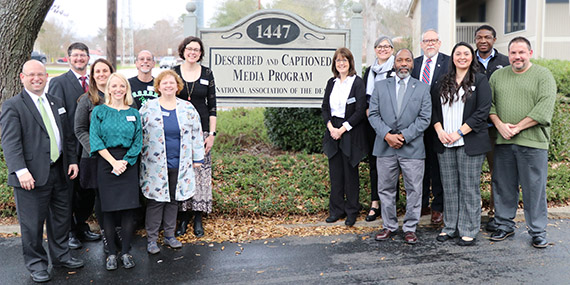 NAD board and DCMP director standing in parking lot by wooden DCMP sign.