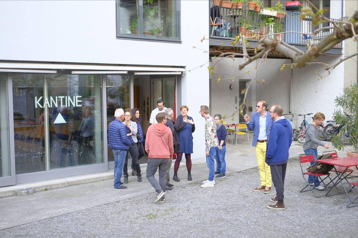 Menschen in einem Innenhof vor einem Lokal mit Glasfront und der Aufschrift Kantine