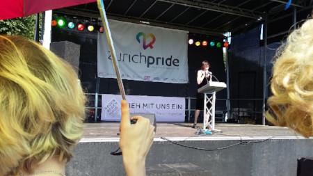 Regenbogenhaus-Banner auf der Polit-Bühne der Pride, Rednerin auf der Bühne