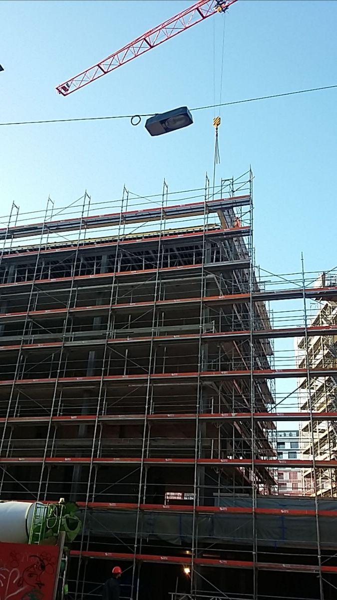 Baustelle mit Gerüst vor blauem Himmel, ein kleiner Durchgang ist zu sehen