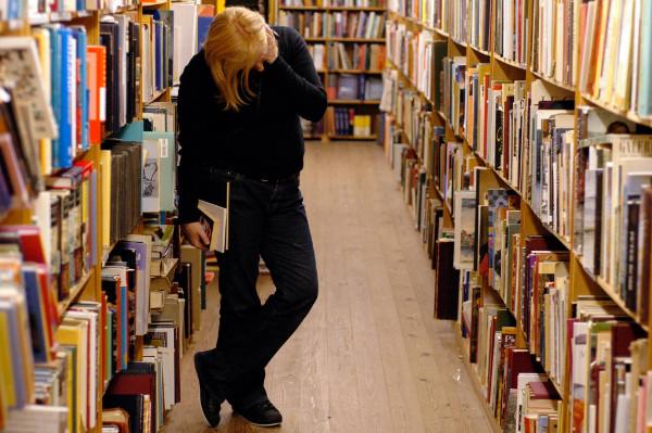 Person in einer Bibliothek mit Holzboden und vollen Holzregalen
