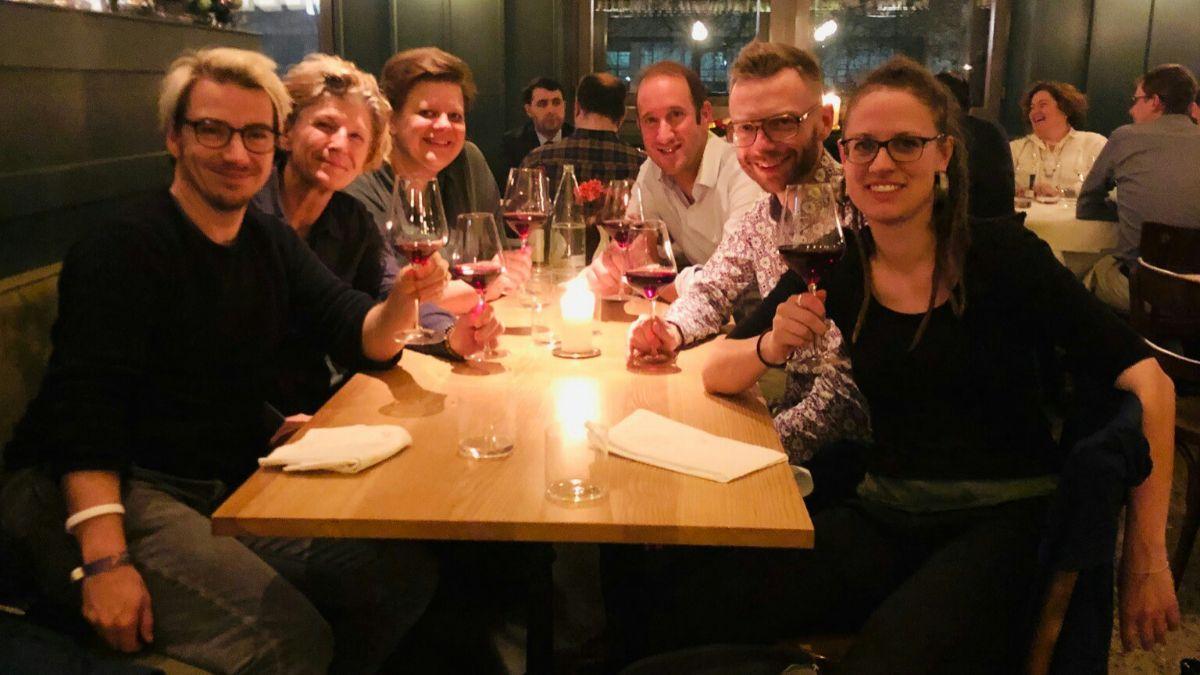 6 Personen mit erhobenen Weingläsern im Restaurant (Vorstand Regenbogenhaus beim Weihnachtsessen)