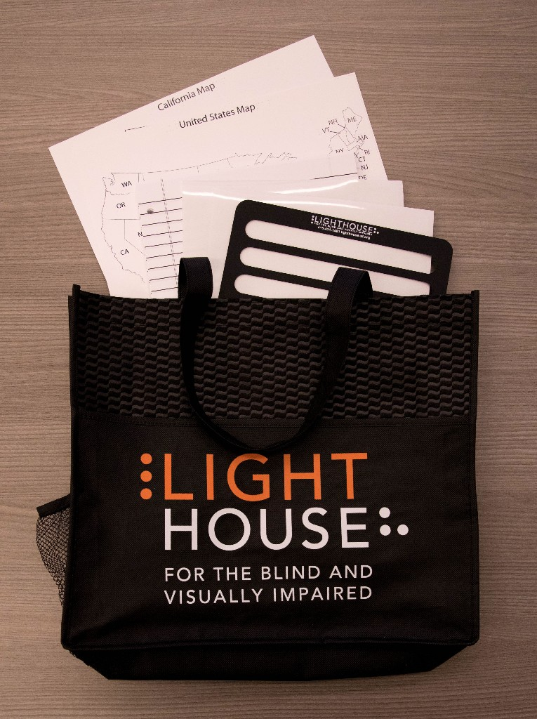 A black LightHouse tote with tactile maps, boldline paper and a full page writing guide peeking out.