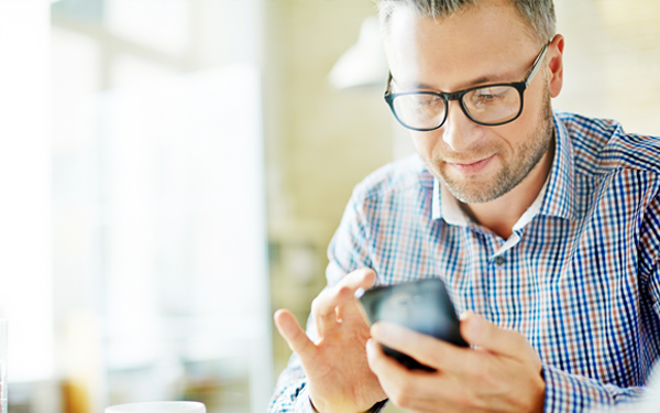Image of man using a smartphone to contact member services