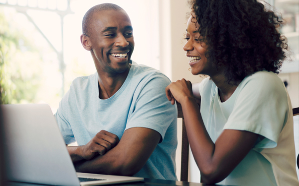Image of a couple smiling at their laptop at home