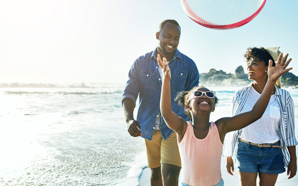 Image of a family playing on a beach during vacation