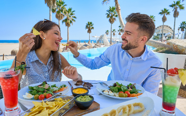 image a couple eating chips and guacamole at a resort