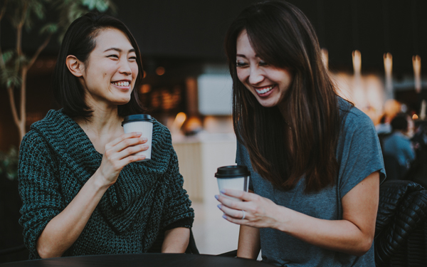 Image of two friends laughing over coffee