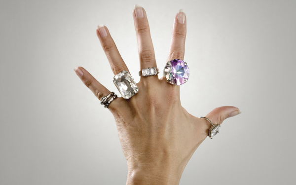 image of a woman's hand adorned with many types of different rings