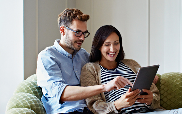 Image of a young couple smiling at their tablet at home