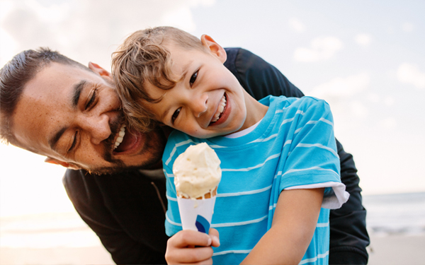 Image of a middle-aged father with his son trying to get his ice cream at the beach