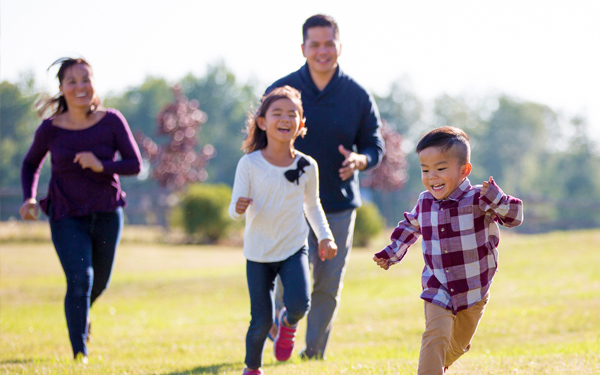 image of a family chasing their son in a park