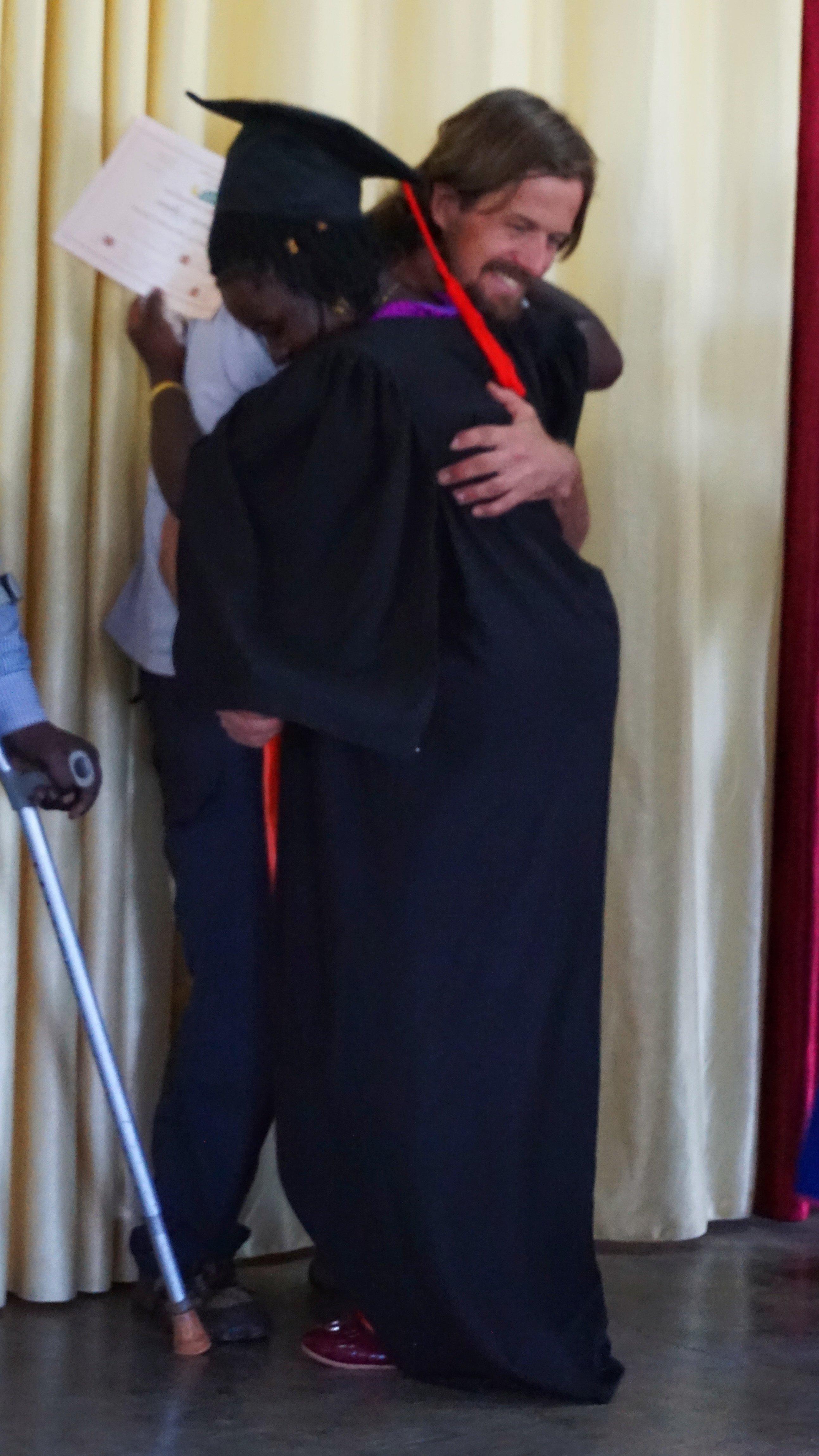 Tim hugs a graduate