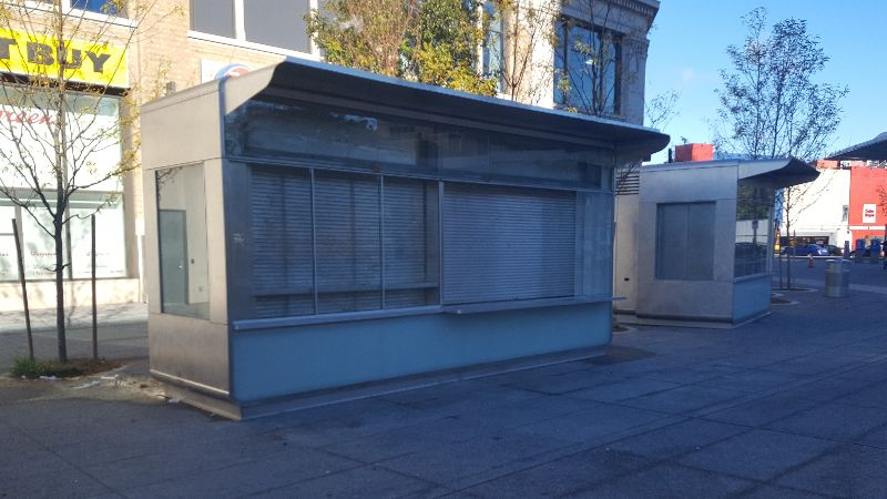 In a public plaza, a small building stands. The building is closed and the doors are shuttered.