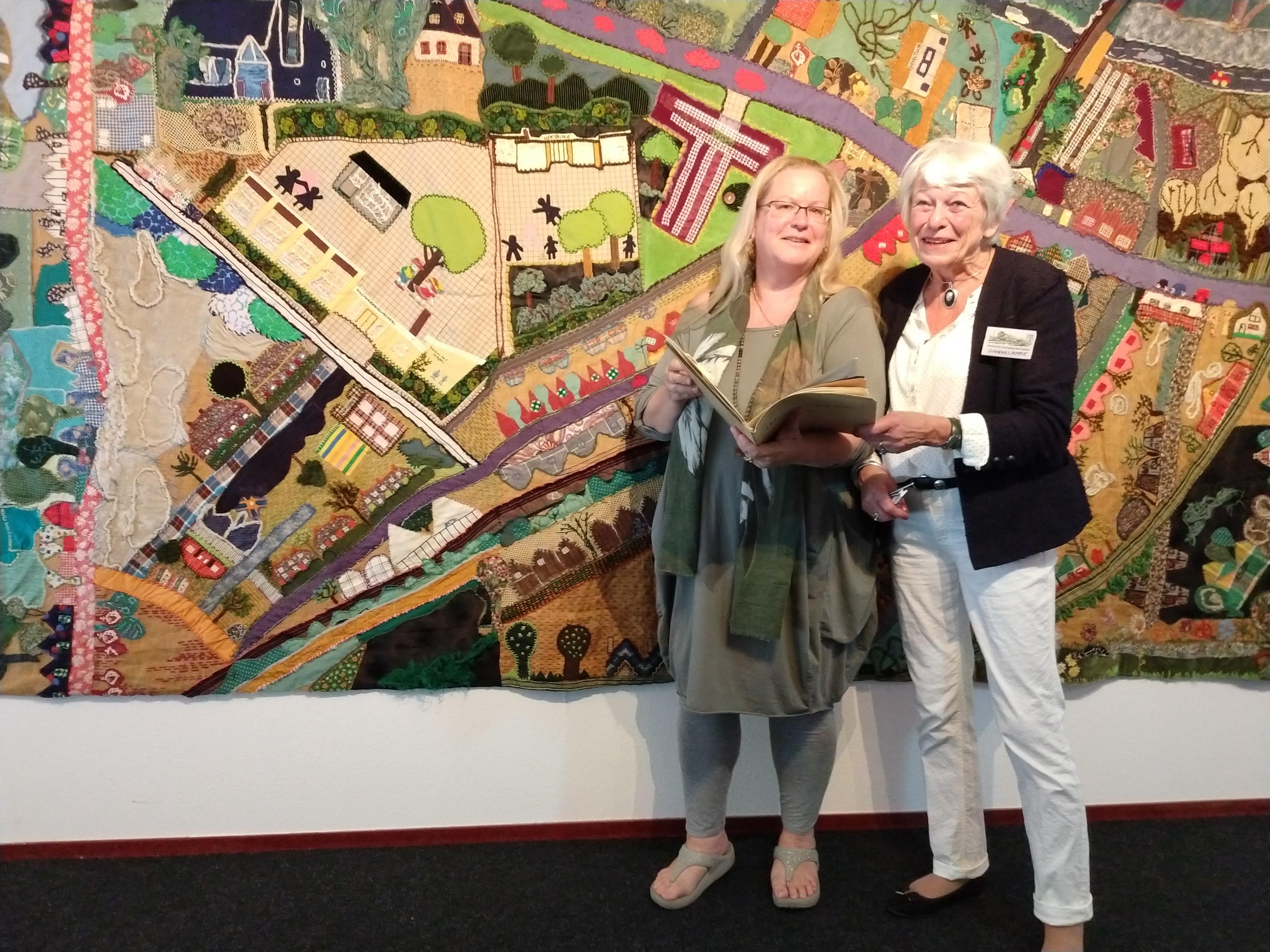 Carola Ruijs (links) overhandigt het fotoalbum aan Anneke Lasterie staande voor het wandkleed (foto: Petra Koek)