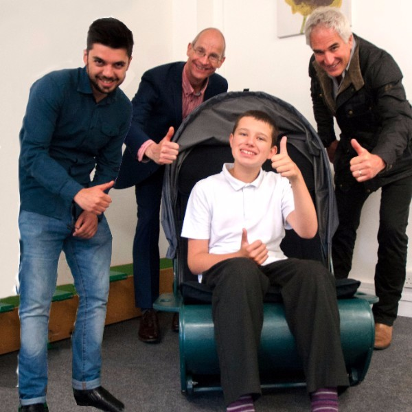 Bradley sitting in the sensory chair giving a thumbs up