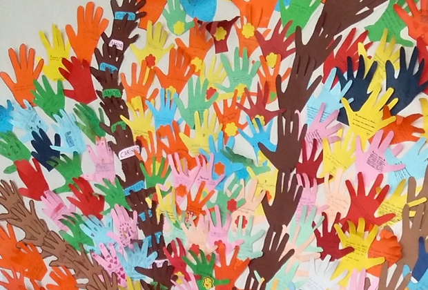 Colourful paper tree made out of hand-shaped cut-outs