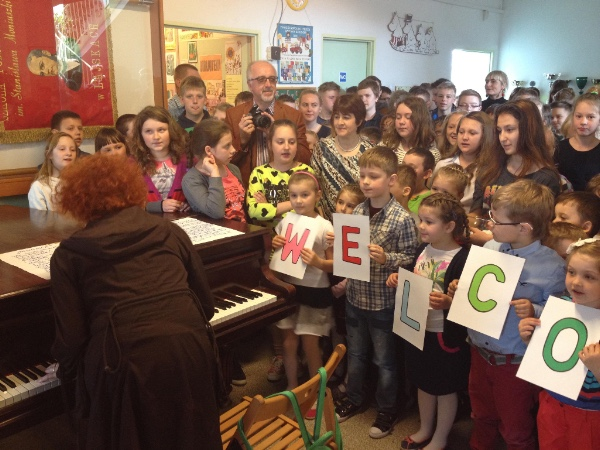 a large group of students and a teacher at the piano